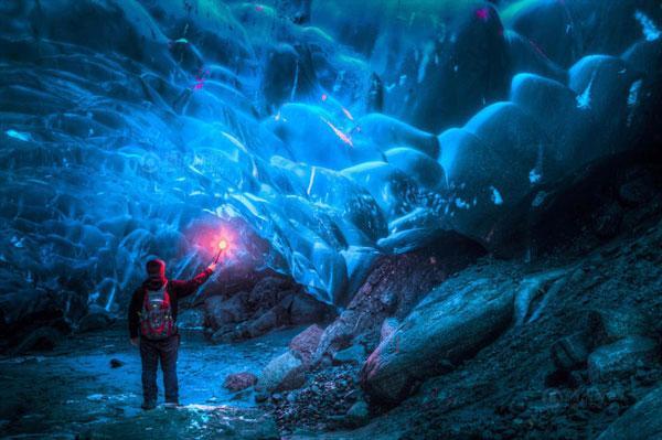 山岩顶部浅蓝色的冰川促生了美丽的冰穴